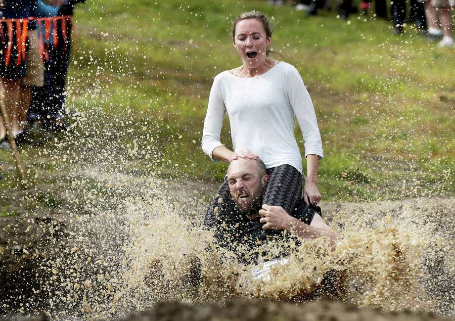 Peter Ver Ploeg carries Virginia Petrovek through the mud pit during the North American Wife Carrying Championship, Saturday, Oct. 8, 2016, at the Sunday River Ski Resort in Newry, Maine. The couple, from Portland, Maine, has been married for one year. Photo: Robert F. Bukaty — AP Photo / Copyright 2016 The Associated Press. All rights reserved.