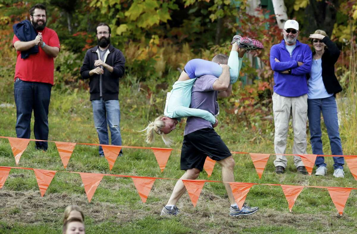 Henry Tabur carries Kim Joyce, both of Pembroke, Mass., while racing in the North American Wife Carrying Championship, Saturday, Oct. 8, 2016, at the Sunday River Ski Resort in Newry, Maine.