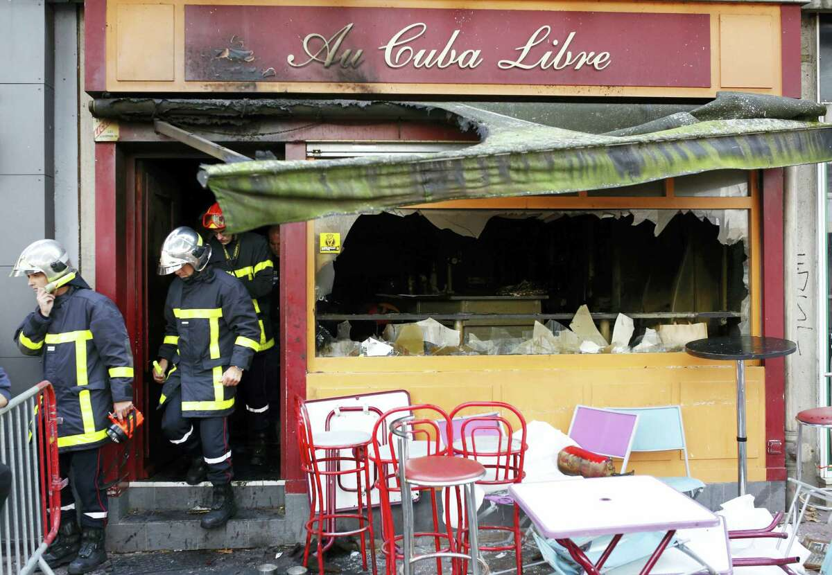 Firefighters leave the bar where a fire broke in Rouen, western France, Saturday Aug.6, 2016. A fire swept through a Friday night birthday party at a bar in the Normandy city of Rouen, killing at least 13 people and injuring six others, French authorities said.