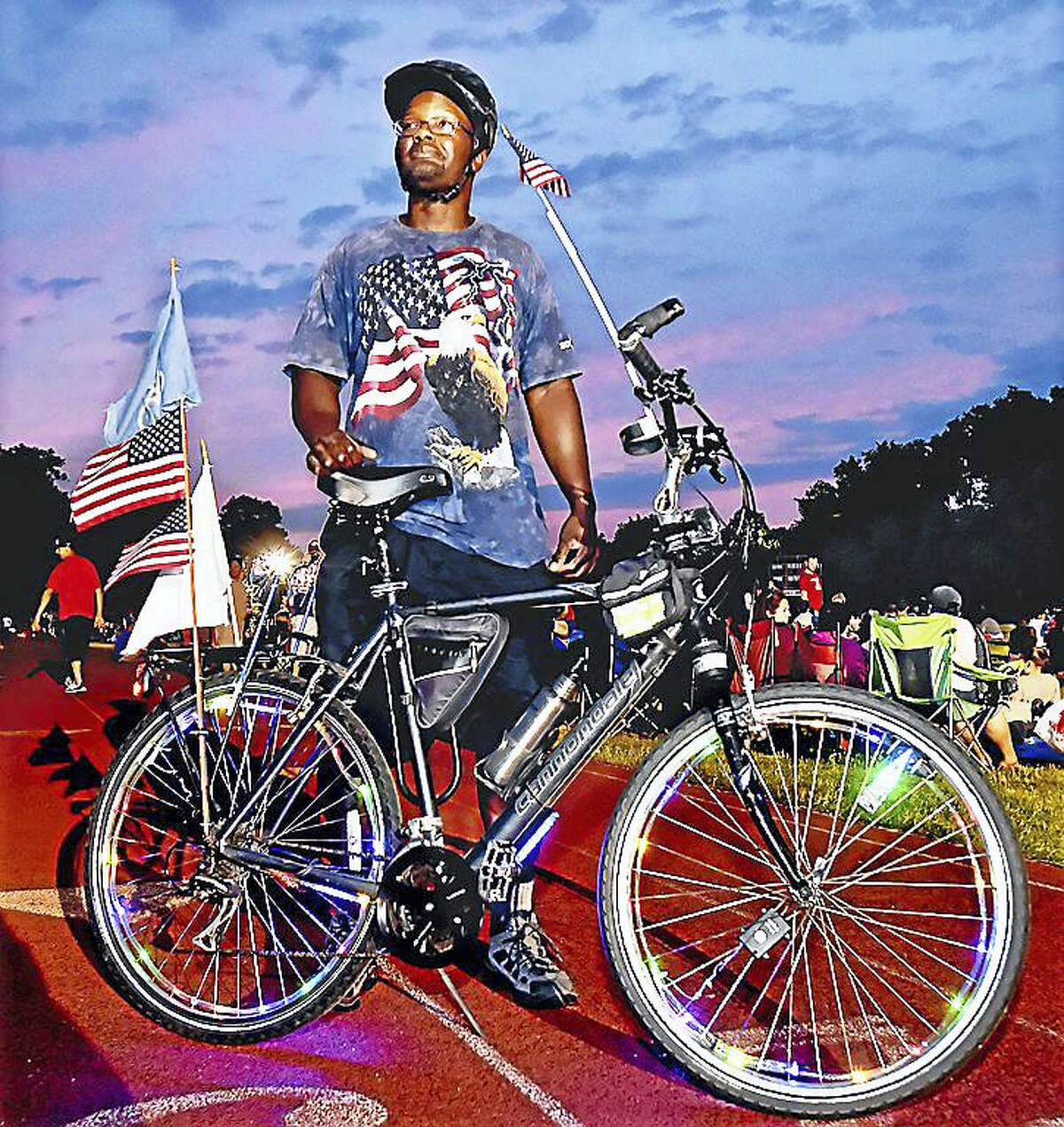 New Haven resident David Joyner and his Cannondale bicycle equipped with colorful lights on the wheels, several American Flags, a state of Connecticut flag and a horn takes a break from his ride at the Wilbur Cross High School Athletic Complex as the sunset creates a majestic sky, to join area residents for the city of New Haven's fireworks display on Independence Day.