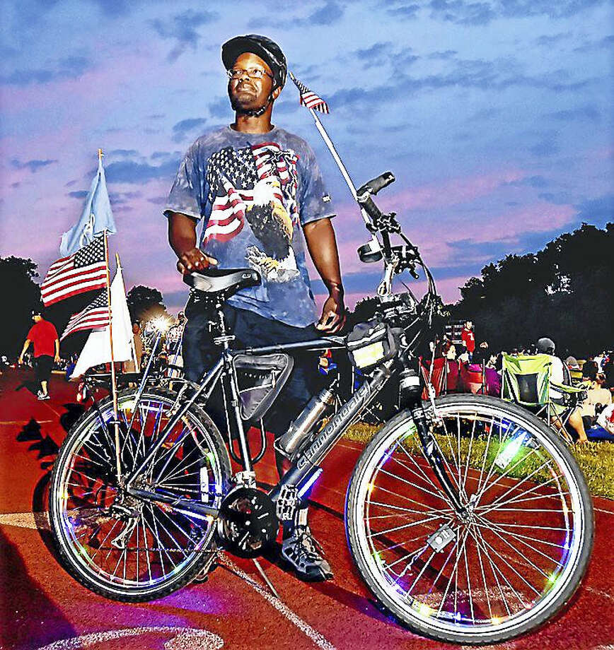 New Haven resident David Joyner and his Cannondale bicycle equipped with colorful lights on the wheels, several American Flags, a state of Connecticut flag and a horn takes a break from his ride at the Wilbur Cross High School Athletic Complex as the sunset creates a majestic sky, to join area residents for the city of New Haven's fireworks display on Independence Day. Photo: Catherine Avalone — New Haven Register   / New Haven RegisterThe Middletown Press