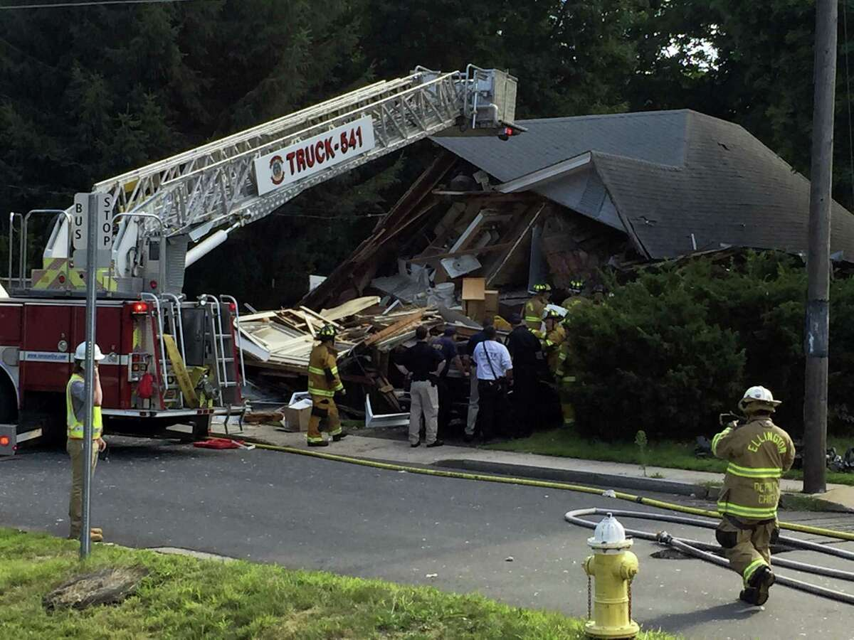 Firefighters work inside the remains of a house that exploded on East Street in Vernon on Thursday.