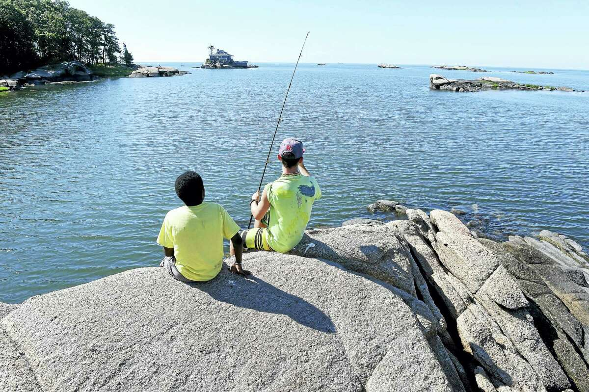 A camper and counselor fish from a rock outcropping at Killian's Point in Branford at Camp Totokett.
