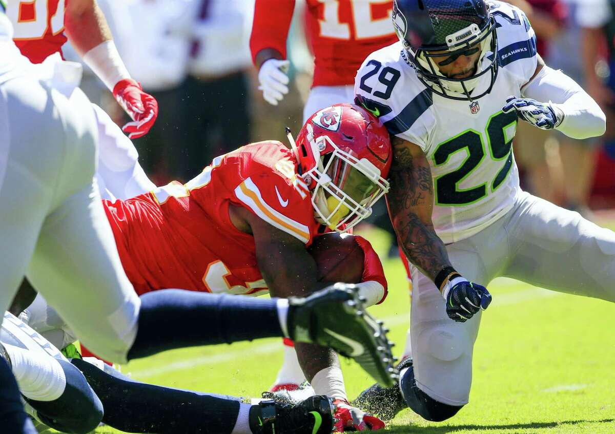 In this Aug. 13, 2016 photo, Kansas City Chiefs running back Spencer Ware (32) is tackled by Seattle Seahawks safety Earl Thomas (29) during the first half of an NFL preseason football game in Kansas City, Mo.