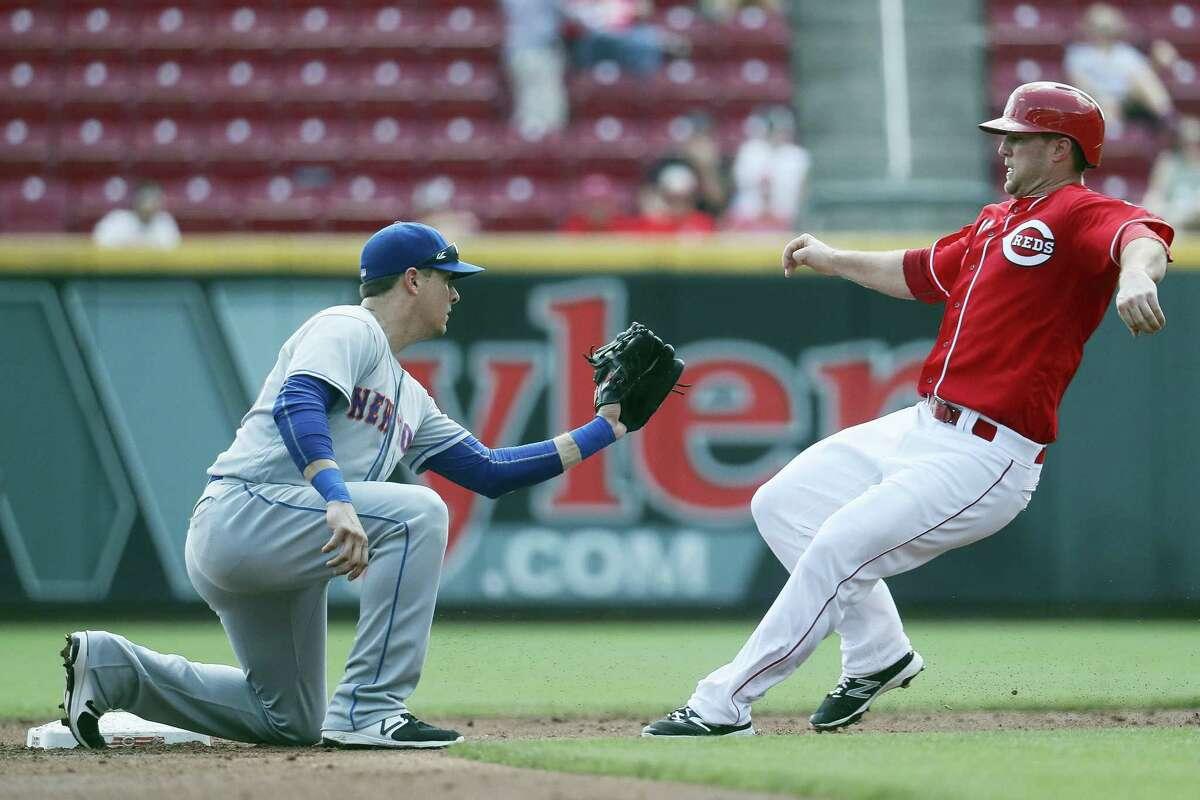 New York shortstop Matt Reynolds, left, tags out Cincinnati Reds' Scott Schebler in the second inning Wednesday. The Mets won 6-3.