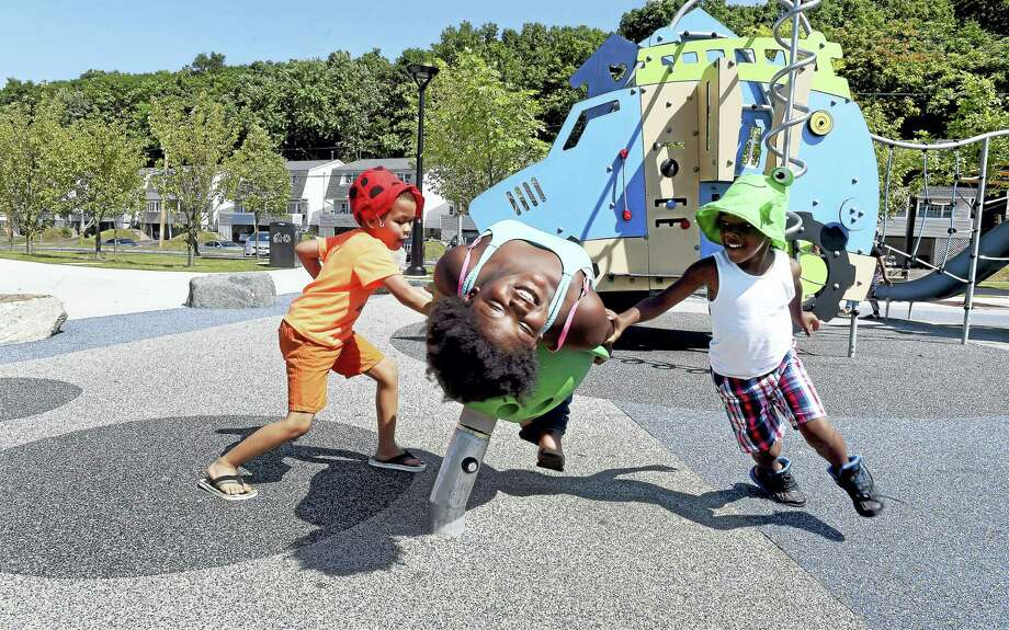 Jasin Douglas, left, 6, of Torrington and Terrace Dean, right, 5, of West Haven spin there cousin, Taylor Davis, center, 7, of Woodbridge, on a chair at Peter Villano Park in Hamden on Friday. Photo: Arnold Gold — New Haven Register