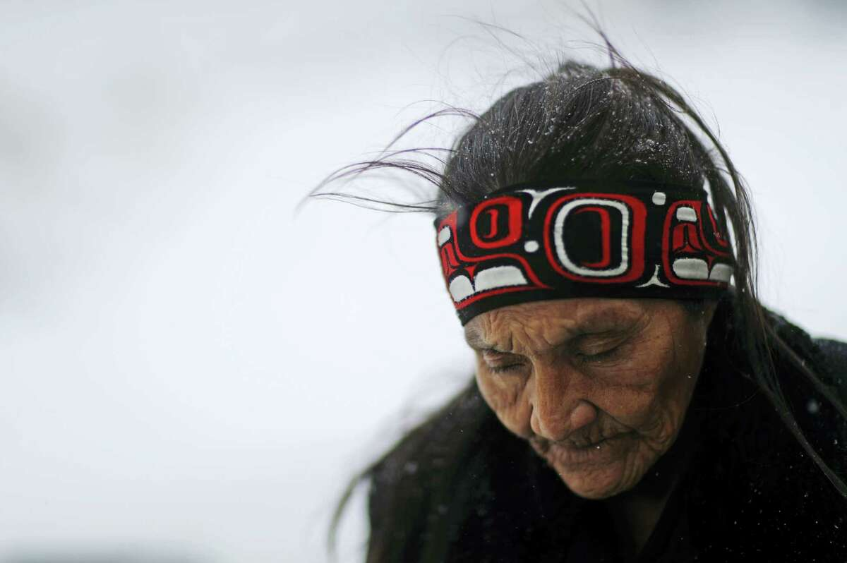 """In this Tuesday, Nov. 29, 2016 photo, Grandma Redfeather of the Sioux Native American tribe walks in the snow to get water at the Oceti Sakowin camp where people have gathered to protest the Dakota Access oil pipeline in Cannon Ball, N.D. """"It's for my people to live and so that the next seven generations can live also,"""" said Redfeather of why she came to the camp. """"I think about my grandchildren and what it will be like for them."""""""