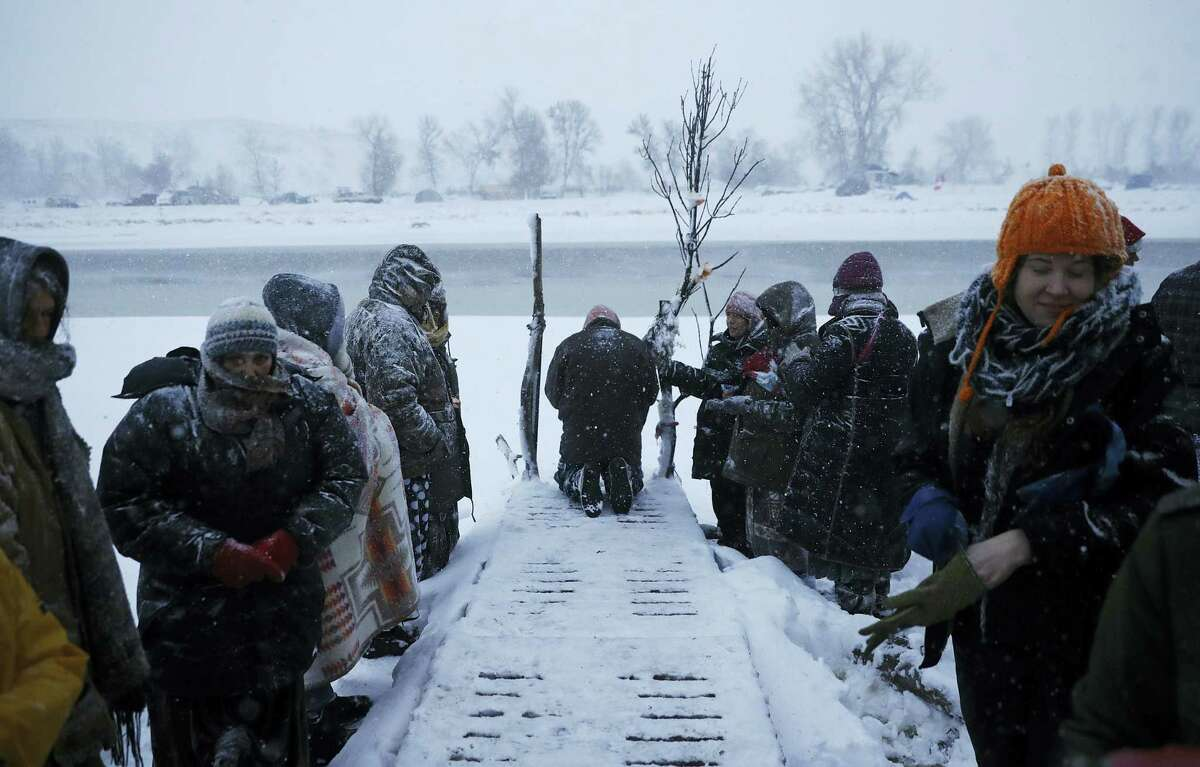 In this Tuesday, Nov. 29, 2016 photo, a person prays along the Cannonball River during a Native American water ceremony at the Oceti Sakowin camp where people have gathered to protest the Dakota Access oil pipeline in Cannon Ball, N.D. So far, those fighting the Dakota Access pipeline have shrugged off the heavy snow, icy winds and frigid temperatures that have swirled around their large encampment on the North Dakota grasslands.