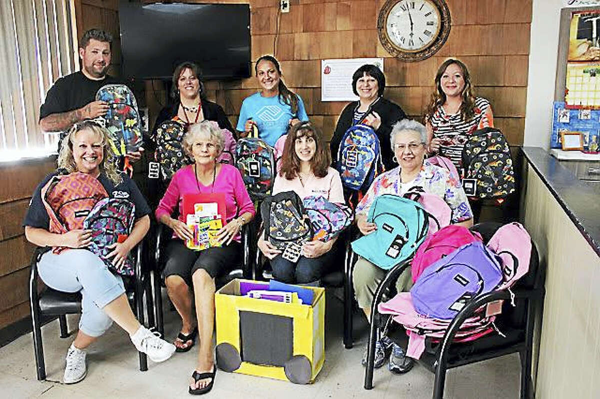 Shown, during the 2015 drive, are, from left, front row: Jennifer Sneider, owner, J Cuts; Marcia Jones, BHcare; Nicole Polifka, Bright Horizons Day Care; and Phyllis Hyde, Barb's Corner Consignment. Back Row: Ross James, barber at J Cuts; Irving School Principal Jennifer Olson; Jen DeLeon, Boys & Girls Club of the Lower Naugatuck Valley; Suzanne Reilly, TEAM Inc.; and Jessica Lanzi, LNV Parent Child Resource Center.