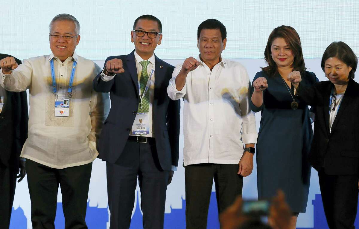 Philippine President Rodrigo Duterte, third from right, poses with a fist bump with business leaders following his address to ASEAN Business and Investment Summit, a parallel summit in the ongoing 28th and 29th ASEAN Summits and other related summits Tuesday, Sept. 6, 2016 in Vientiane, Laos.