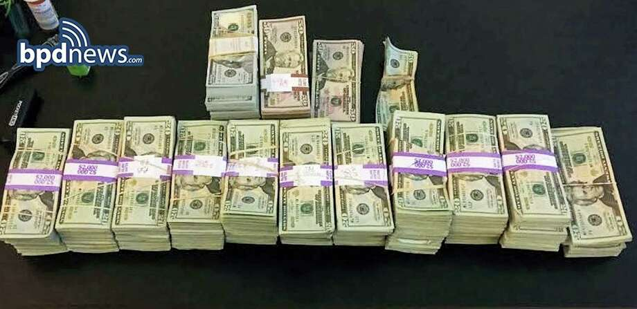 """In this photo released July 5, 2016, by the Boston Police Department, stacks of money totaling about $187,000 that were left in a taxi are displayed in Boston. Boston police said cab driver Raymond """"Buzzy"""" MacCausland picked up a rider in Boston on Saturday who left a backpack containing the money in the taxi. After being unable to locate the man, MacCausland drove to police headquarters to turn in the cash. The unidentified rider was reunited with his money, which turned out had been inherited. MacCausland received a $100 reward. Photo: Boston Police Department Via AP    / BOSTON POLICE DEPARTMENT"""