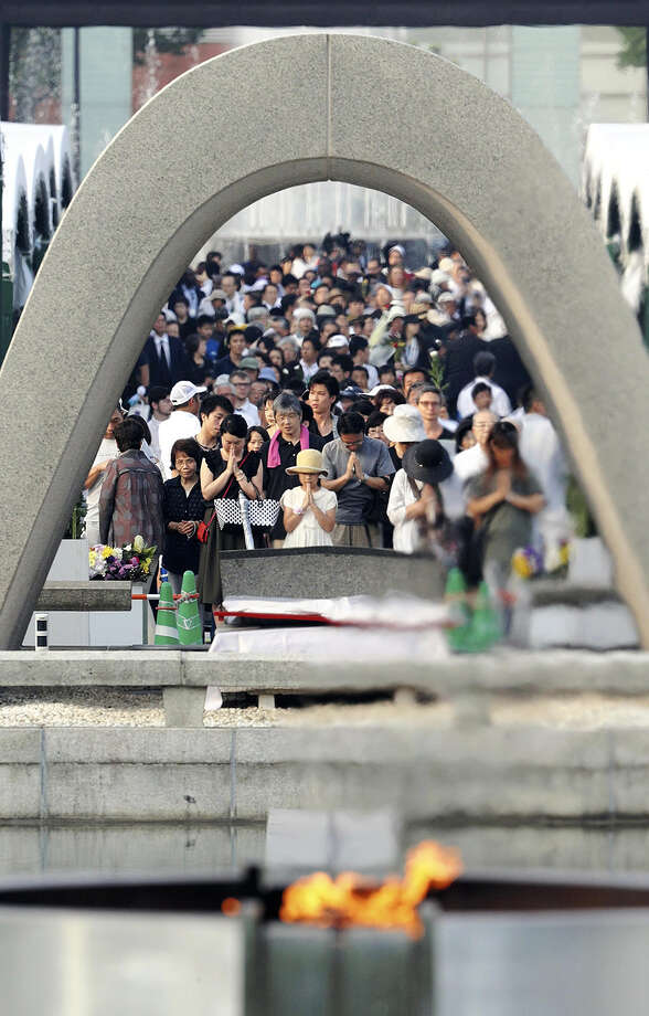 People pray in front of the Cenotaph for the atomic bomb victims on Saturday morning at the Hiroshima Peace Memorial Park. Photo: The Japan News/Yomiuri / The Japan News/Yomiuri