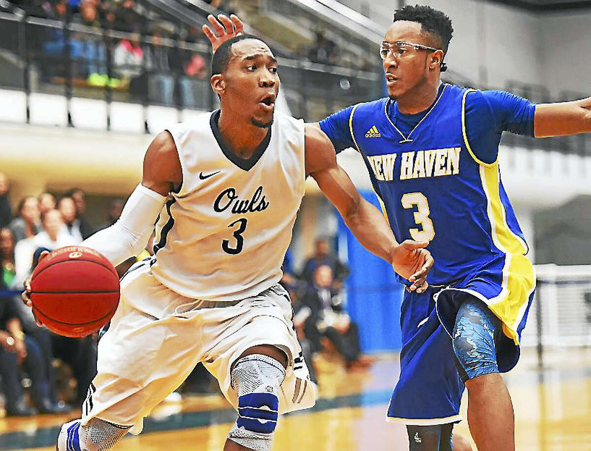 SCSU senior guard Michael Mallory looks for an opening in the paint as UNH freshman guard Elijah Bailey defends Wednesday at the Moore Field House at Southern Connecticut State University.