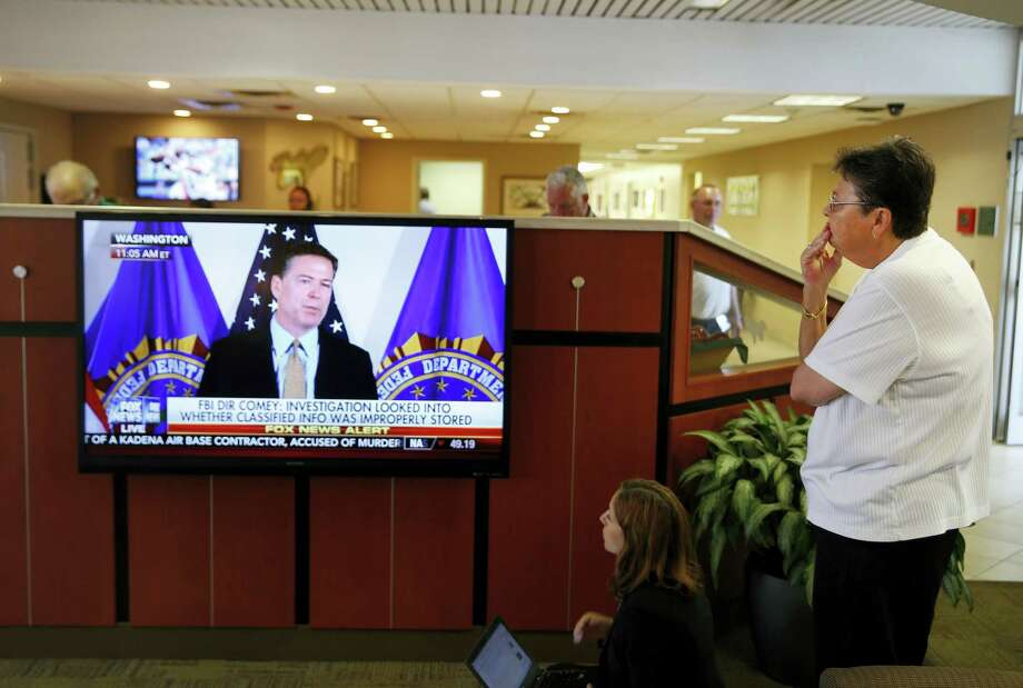 A woman watches as FBI Director James Comey announces the results of his department's investigation into former Secretary of State and Democratic presidential candidate Hillary Clinton's handling of classified emails, Tuesday, July 5, 2016, in Charlotte, N.C. Clinton is expected to appear with at President Barack Obama in Charlotte later Tuesday. Photo: AP Photo/John Bazemore    / Copyright 2016 The Associated Press. All rights reserved. This material may not be published, broadcast, rewritten or redistribu