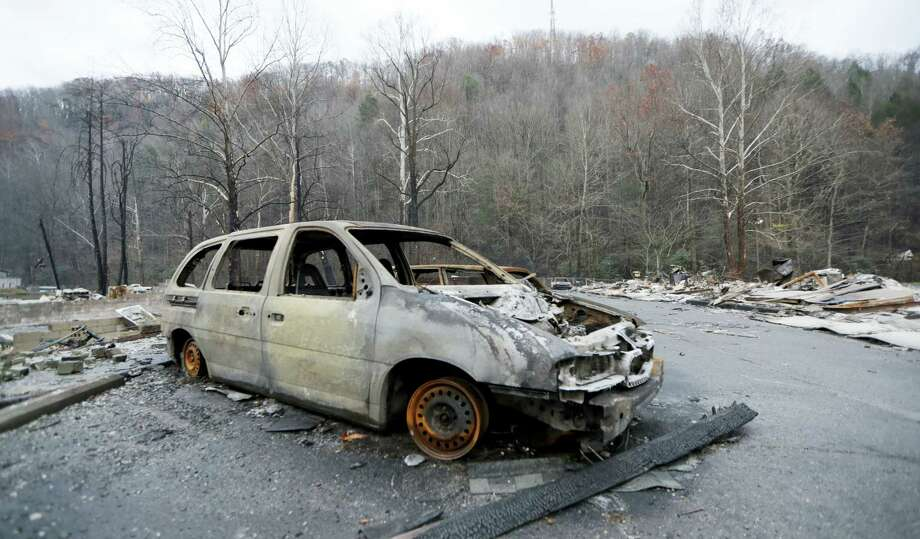 A burned car sits in a parking lot Wednesday, Nov. 30, 2016, in Gatlinburg, Tenn., after a wildfire swept through the area Monday. Three more bodies were found in the ruins of wildfires that torched hundreds of homes and businesses in the Great Smoky Mountains area, officials said Wednesday. Photo: AP Photo/Mark Humphrey    / Copyright 2016 The Associated Press. All rights reserved.