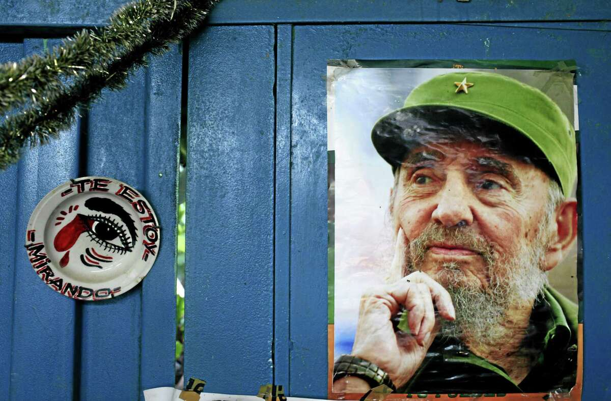 """A poster of Cuba's Fidel Castro hangs on the wall of a food market next to a plate that reads in Spanish, """"I'm looking at you,"""" in Havana, Cuba, in this 2013 photo."""
