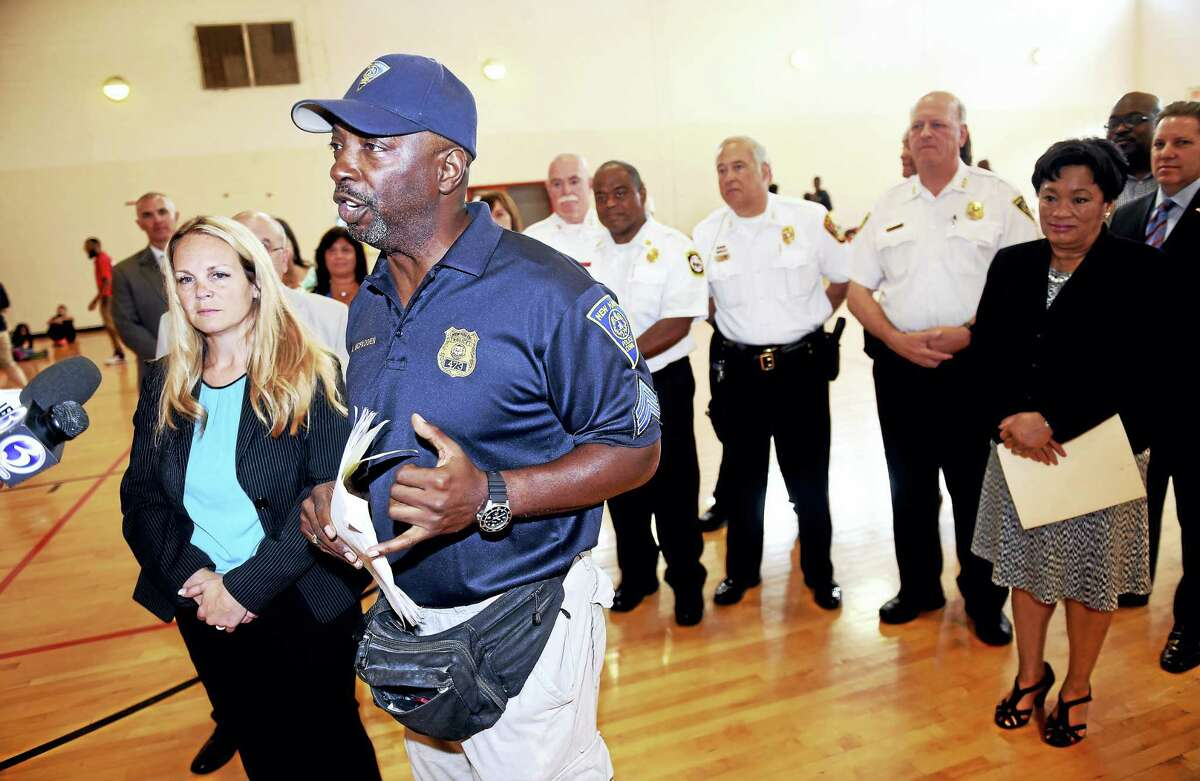 New Haven police Sgt. Albert McFadden, director of the New Haven Police Athletic League Camp, speaks with the press about the summer camp on the first day at Wilbur Cross High School in New Haven Tuesday. At far left is New Haven police Sgt. Elisa Tuozzoli, co-director of the camp.