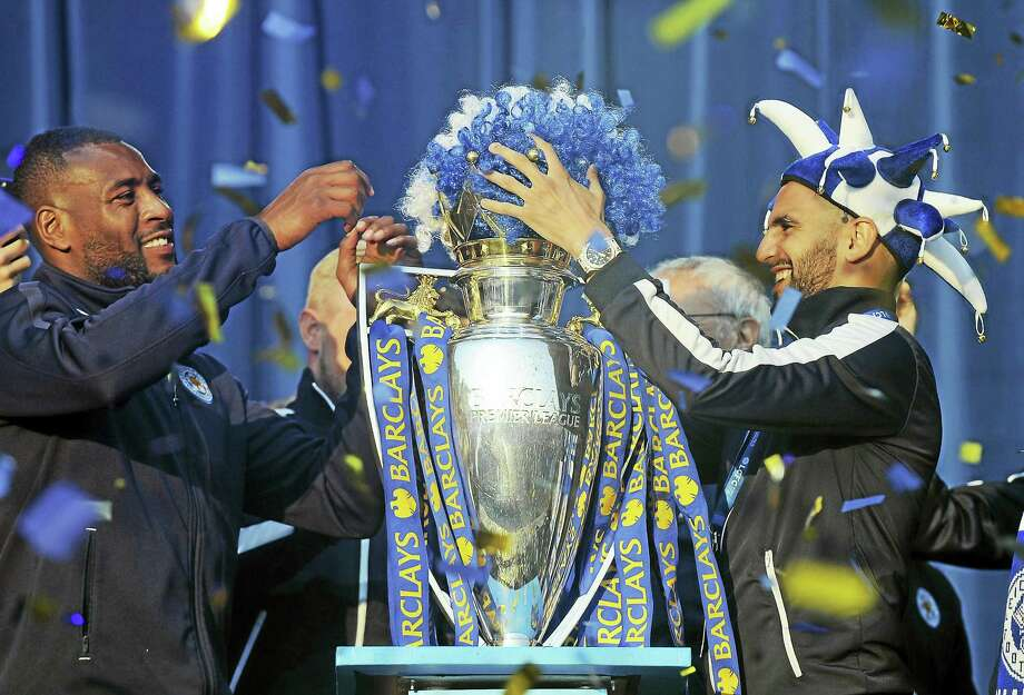 Leicester City captain Wes Morgan, left, and Leicester's Riyad Mahrez place a Leicester wig in club colours on the Premier League Trophy during a victory parade. Photo: The Associated Press File Photo   / Copyright 2016 The Associated Press. All rights reserved. This material may not be published, broadcast, rewritten or redistribu