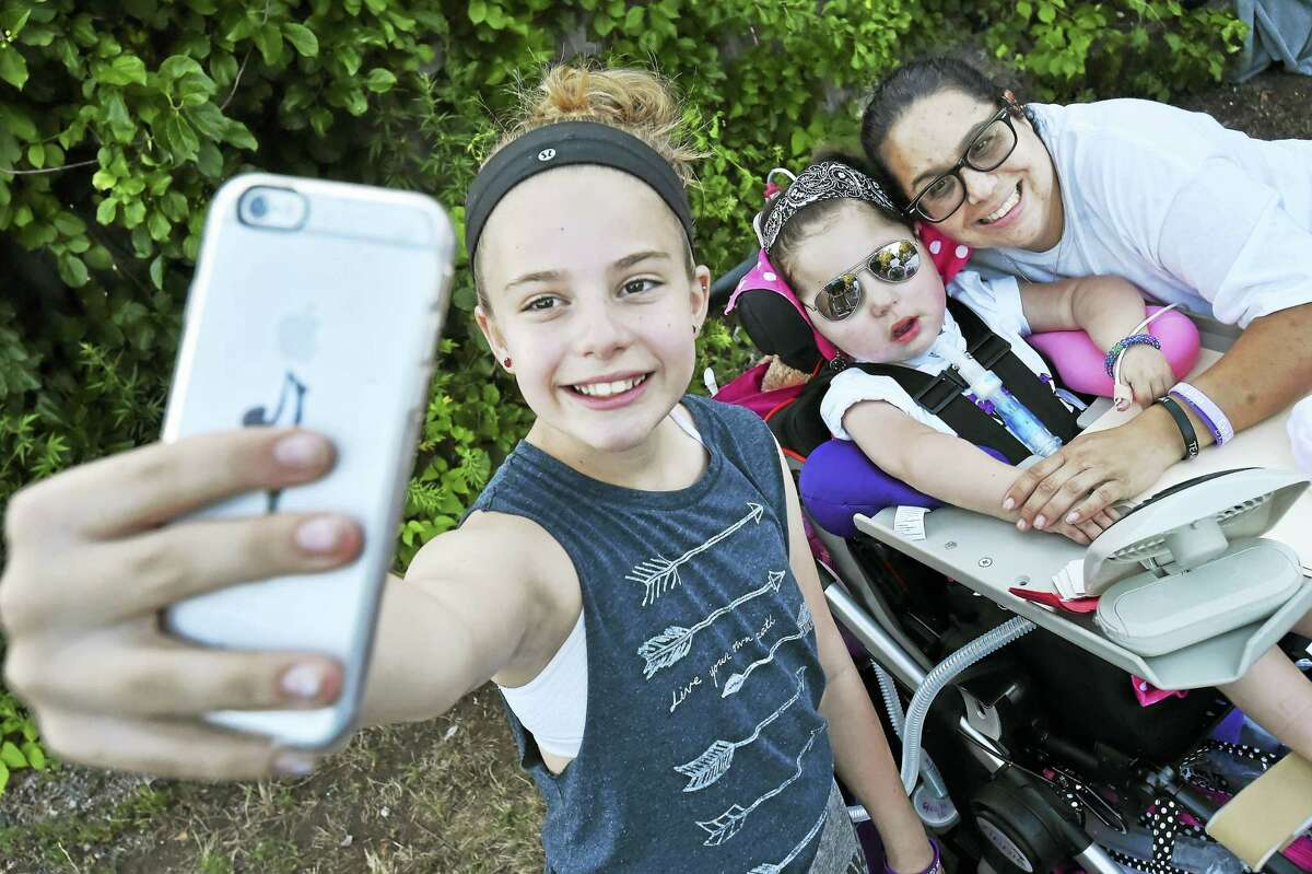 """Ella Montagna, 11, of Stratford takes a selfie with 5-year-old Eva Grace Kelly and her mother, Melissa Lombardo Kelly of West Haven, at """"Bike Night for Eva"""" at the Valley Diner in Derby Tuesday,"""