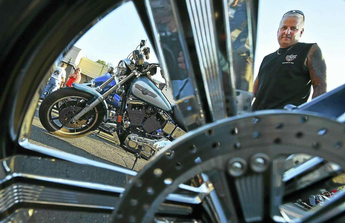 """Stratford resident John Lombardo gets a closer look at a Harley-Davidson Tuesday at """"Bike Night for Eva,"""" at the Valley Diner in Derby. The fundraiser is to pay for medical bills for his cousin, Eva Grace Kelly."""