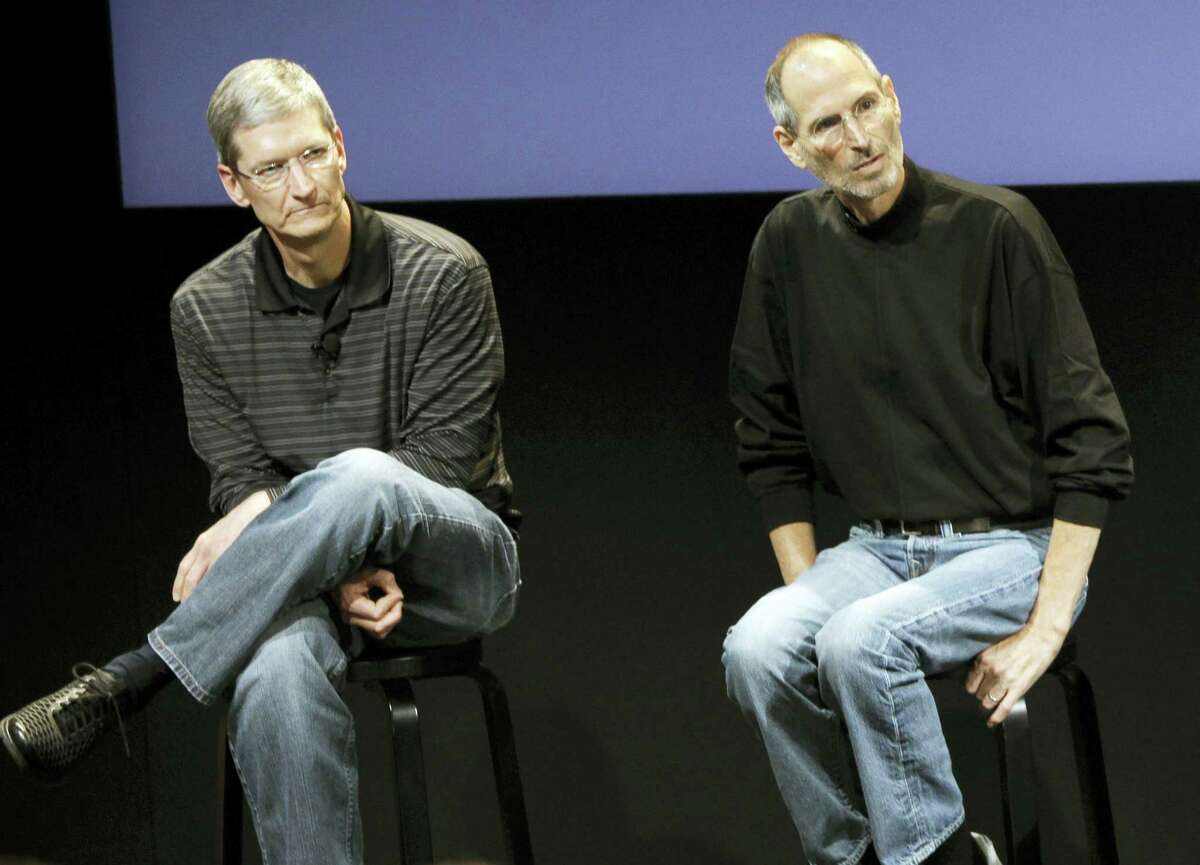 """This July 16, 2010 photo shows Apple's Tim Cook, left, and Steve Jobs, right, during a meeting at Apple in Cupertino, Calif. Apple wants to encourage millions of iPhone owners to register as organ donors through a software update that will add an easy sign-up button to the health information app that comes installed on every smartphone the company makes. CEO Cook says he hopes the new software, set for limited release in early July 2016, will help ease a critical and longstanding donor shortage. He said the problem hit home when his friend and former boss, Apple co-founder Jobs, endured an """"excruciating"""" wait for a liver transplant in 2009."""