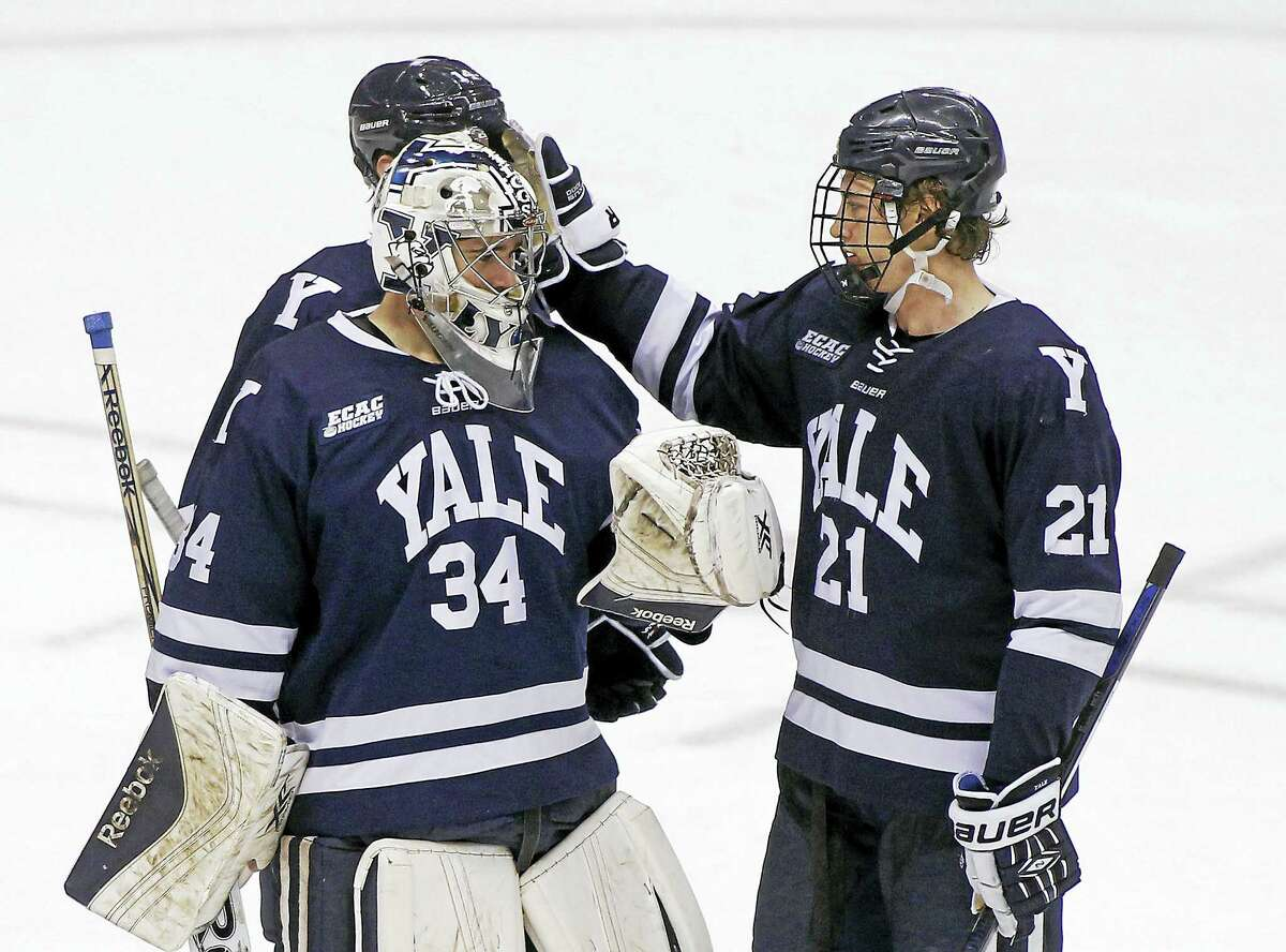 Yale's John Hayden (21) congratulates goalie Alex Lyon (34) after the team's 4-0 victory over Arizona State during an NCAA college hockey game at the Desert Hockey Classic tournament, Friday, Jan. 8, 2016, in Glendale, Ariz. (AP Photo/Ralph Freso)