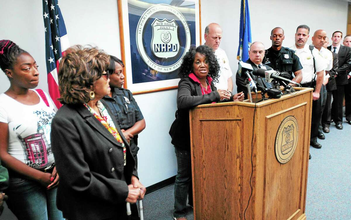 Anthony Stevenson's wife, Monique, far left, and mother, Leola Davis, second from left, listen to his sister, Roselyn McKinnie, at podium, thank police at a press conference at the New Haven Police Department announcing the arrest of Semmion Watson in the slaying of Anthony Stevenson in 2013.