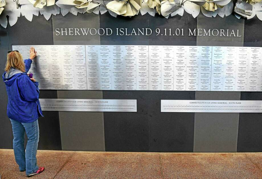 Sue Monroe of Stratford places her hand over the plaque honoring Thomas Brennan at the Sherwood Island 9/11 Memorial at Sherwood Island in Westport in this photo from last year. Photo: New Haven Register File Photo