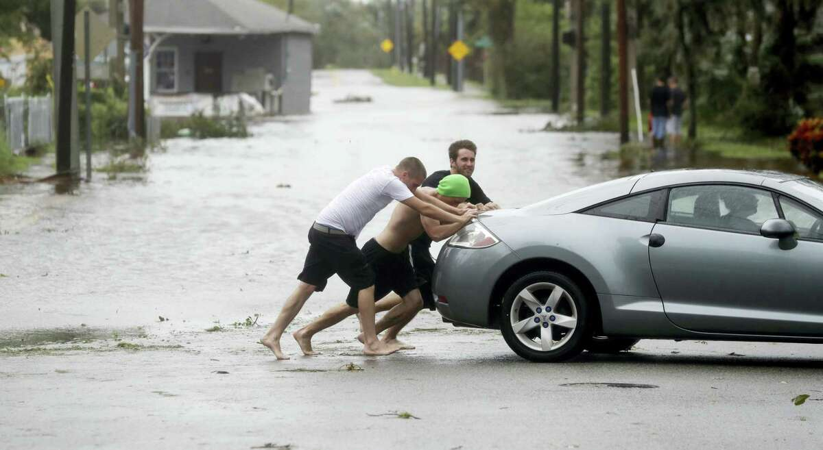 Noah Simons steers as his car is pushed out of flood waters caused by Hurricane Matthew, Friday, Oct. 7, 2016, in Daytona Beach, Fla. Hurricane Matthew spared Florida's most heavily populated stretch from a catastrophic blow Friday but threatened some of the South's most historic and picturesque cities with ruinous flooding and wind damage as it pushed its way up the coastline.