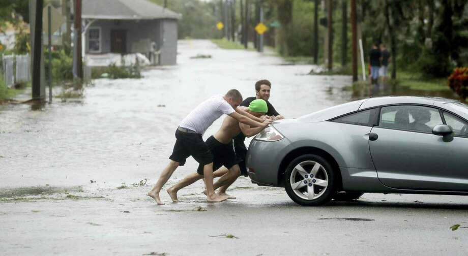 Noah Simons steers as his car is pushed out of flood waters caused by Hurricane Matthew, Friday, Oct. 7, 2016, in Daytona Beach, Fla. Hurricane Matthew spared Florida's most heavily populated stretch from a catastrophic blow Friday but threatened some of the South's most historic and picturesque cities with ruinous flooding and wind damage as it pushed its way up the coastline. Photo: (AP Photo/Eric Gay) / Copyright 2016 The Associated Press. All rights reserved.