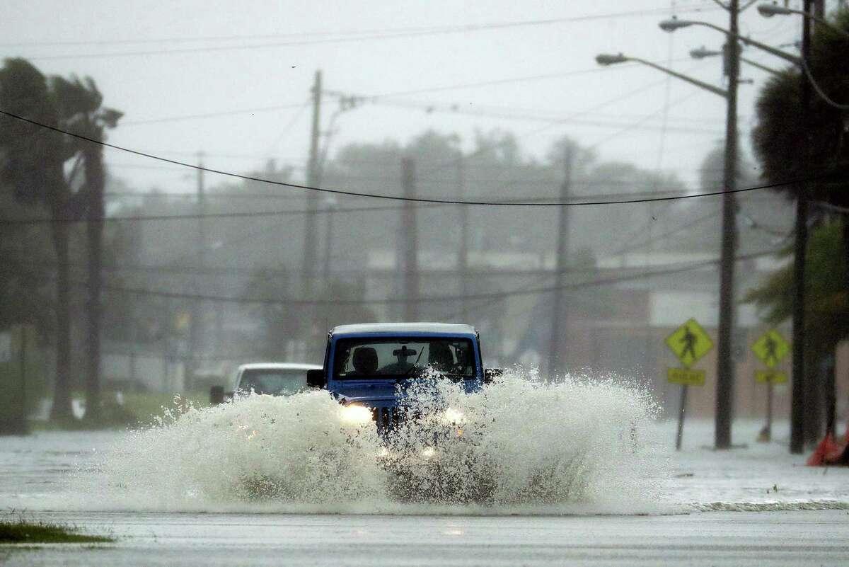 Cars drive through a flooded street as Hurricane Matthew moves through Daytona Beach, Fla. Friday, Oct. 7, 2016.