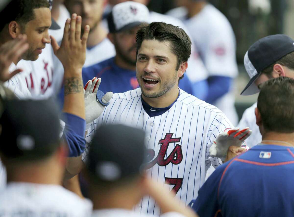 New York's Travis d'Arnaud is greeted by teammates after hitting a home run during the fourth inning against the Miami Marlins at Citi Field Monday. The Mets defeated the Marlins 8-6.