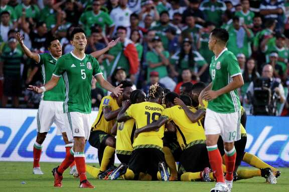 Mexico's Jesus Molina (5) has a look of resignation as Jamaica players celebrate a goal by Kemar Lawrence in the second half of Sunday's Gold Cup semifinal.