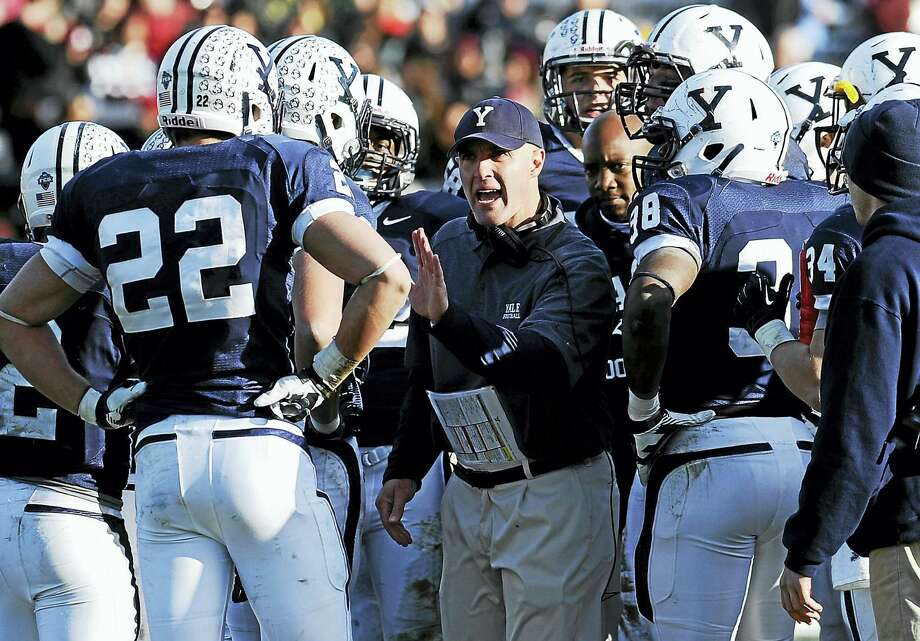 Yale head coach Tony Reno, center, talks to his team during the second half against Harvard at Yale Bowl Nov. 23, 2013, in New Haven. Harvard won 34-7. Photo: Jessica Hill — THE ASSOCIATED PRESS   / FR125654 AP