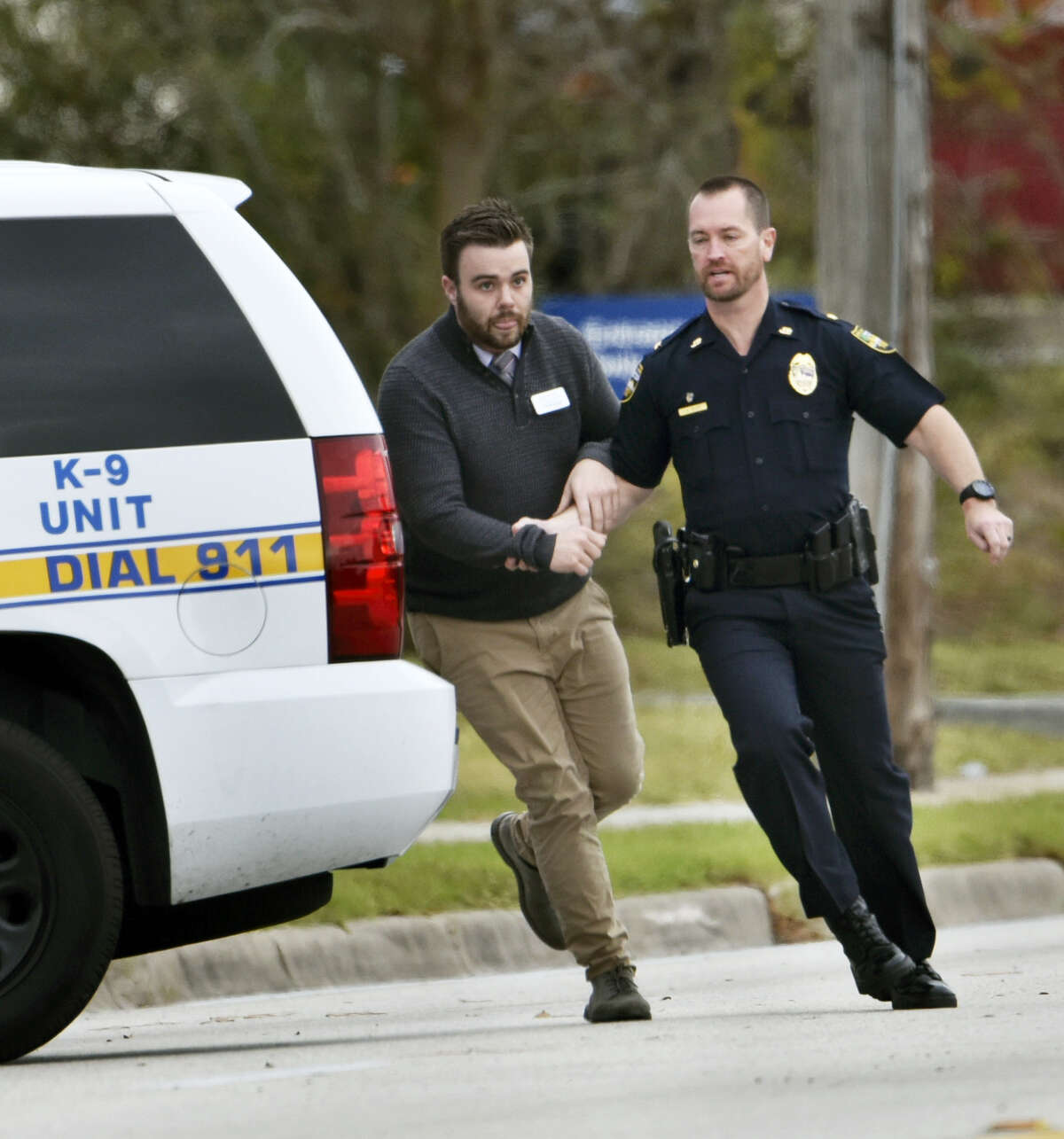 A police officer leads a hostage to safety during an attempted robbery at Community First Credit Union Thursday, Dec. 1, 2016, in Jacksonville, Fla.