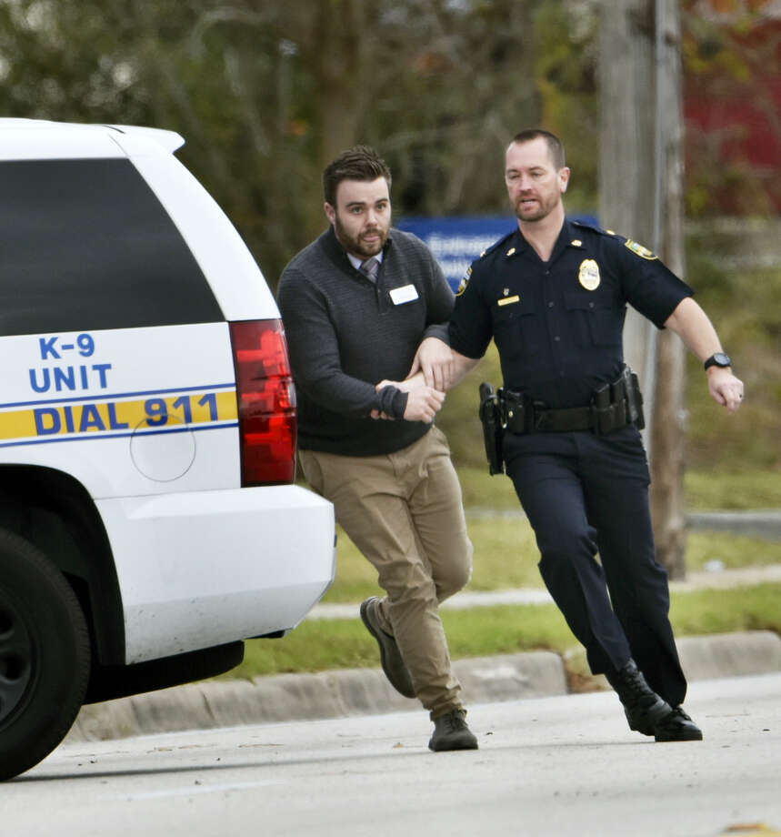 A police officer leads a hostage to safety during an attempted robbery at Community First Credit Union Thursday, Dec. 1, 2016, in Jacksonville, Fla. Photo: Will Dickey — The Florida Times-Union Via AP / Will Dickey/Florida Times-Union
