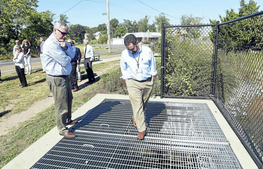Arnold Gold — New Haven Register    Bob Kaliszewski,left, of the state Department of Energy and Environmental Protection and DEEP Commissioner Robert Klee, center, look over the self-regulating tide gates at the mouth of Old Field Creek in West Haven Friday. Photo: Journal Register Co.