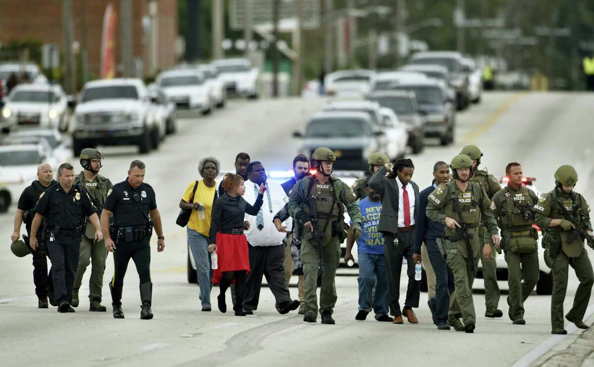 Police officers escort hostages safely across Edgewood Avenue West after a gunman held them during an attempted robbery at Community First Credit Union Thursday, Dec. 1, 2016, in Jacksonville, Fla.
