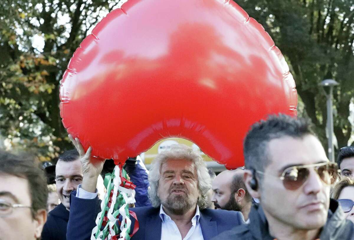 Five Star Movement leader Beppe Grillo holds a heart-shaped balloon adorned with strips in the colors of the Italian flag during a demonstration to support a no vote in Sunday's constitutional referendum in Rome.
