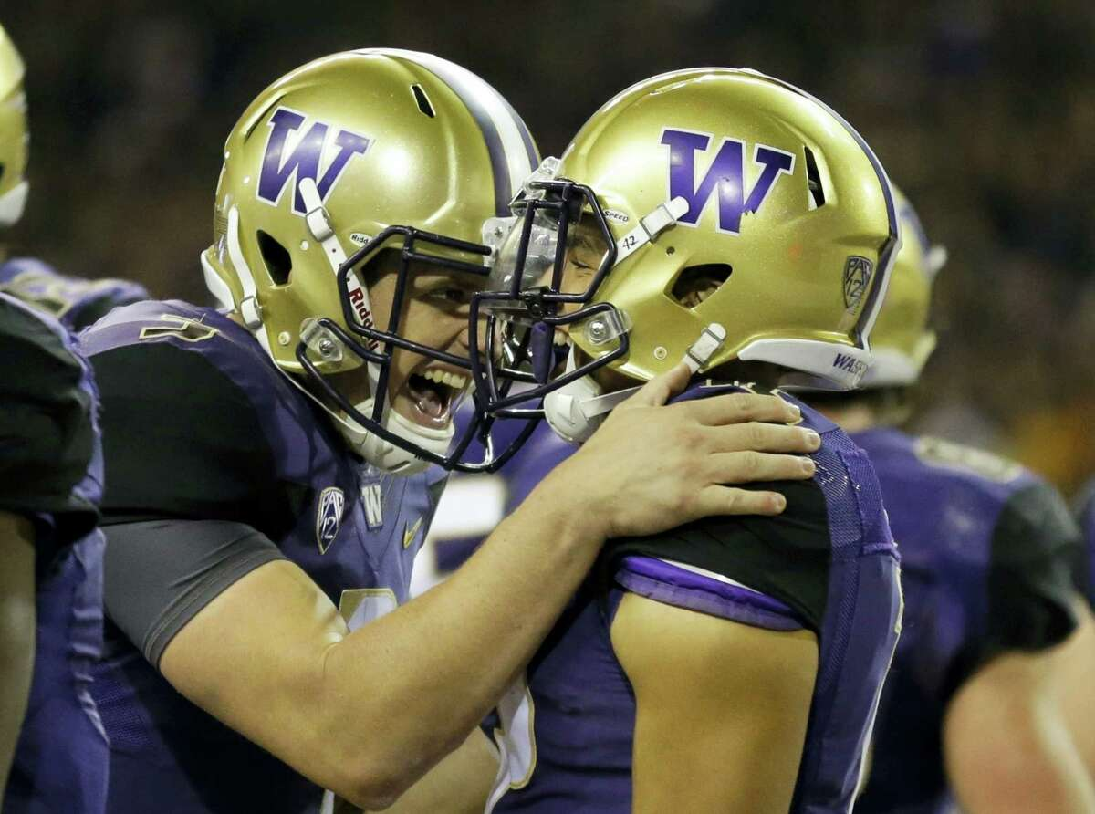 In this Sept. 30, 2016 photo, Washington quarterback Jake Browning, left, celebrates with wide receiver Aaron Fuller after Fuller caught a pass from Browning for a touchdown in the second half of an NCAA college football game, in Seattle. The Huskies are coming off smashing Stanford and have a top-five ranking for the first time since the end of the 2001 season.
