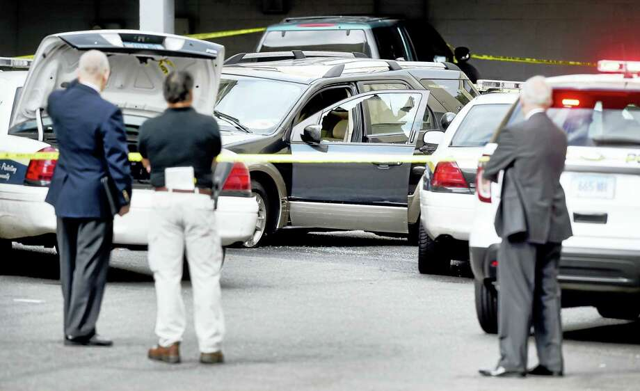 New Haven and state police investigate the scene of a man shot by police in his car, center, earlier Tuesday morning at Church Street South in New Haven. Photo: Arnold Gold — New Haven Register