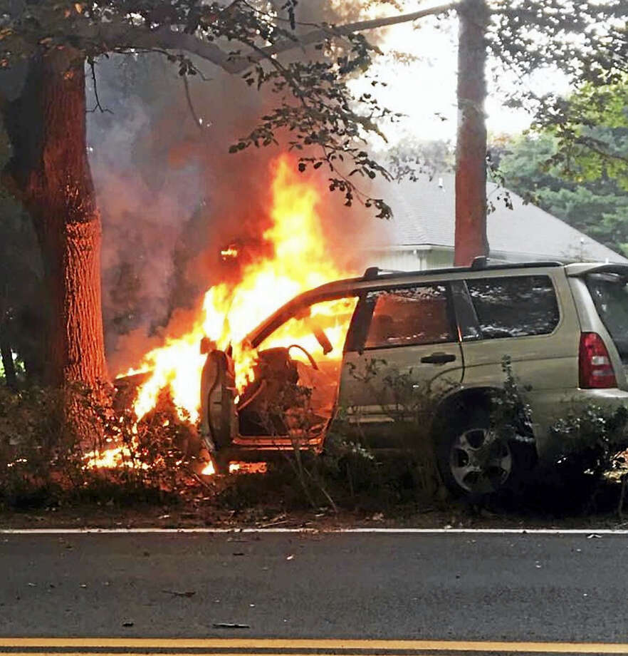 A woman's car caught on fire after crashing into a tree Sunday evening, police said. Photo: Courtesy Of Branford POlice Dept.