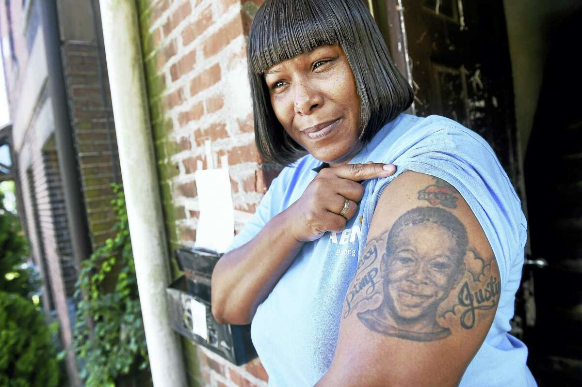 Tracey Suggs shows off a tattoo memorializing her late son, Justus, outside of her home in New Haven Thursday.