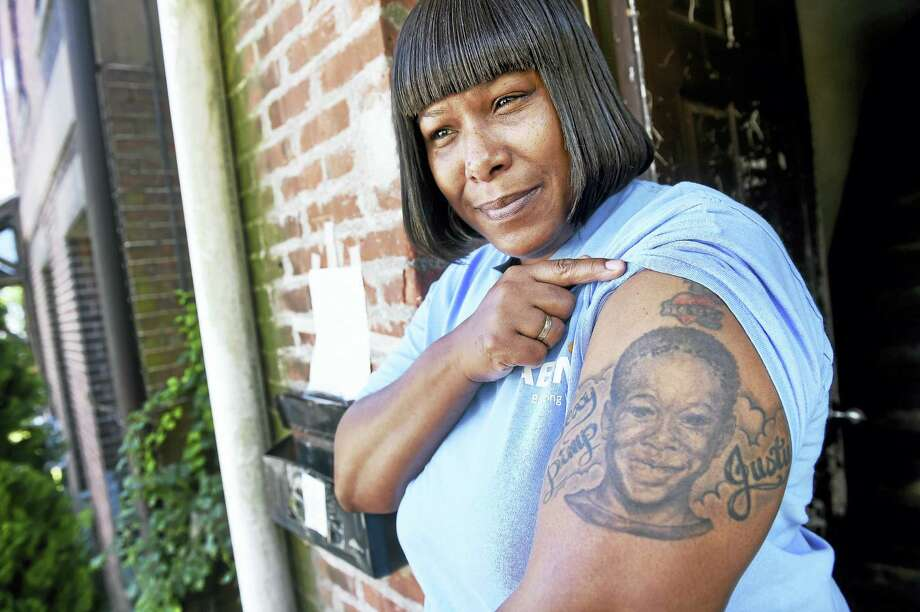 Tracey Suggs shows off a tattoo memorializing her late son, Justus, outside of her home in New Haven Thursday. Photo: Arnold Gold — New Haven Register