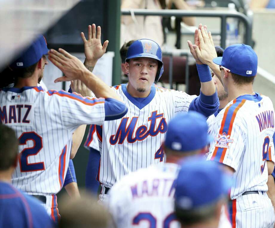 Wilmer Flores, center, is greeted by teammates after scoring during the fourth inning on Sunday. Photo: Seth Wenig — The Associated Press   / Copyright 2016 The Associated Press. All rights reserved. This material may not be published, broadcast, rewritten or redistribu