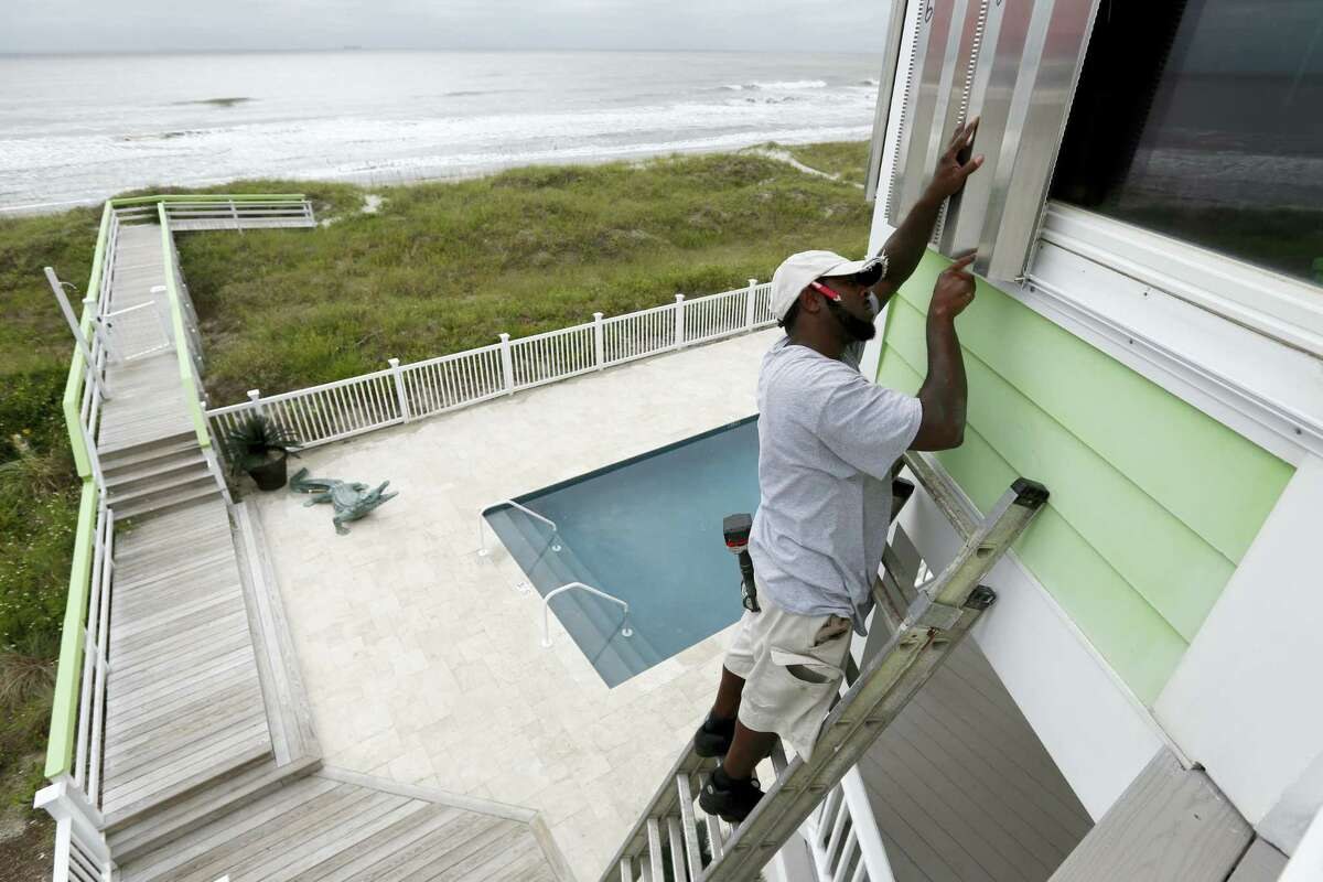 Dimitri Pinckney installs hurricane shutters in advance of Hurricane Matthew on the Isle of Palms, S.C., Wednesday, Oct. 5, 2016. Hurricane Matthew is expected to affect the South Carolina coast by the weekend. Gov. Nikki Haley announced Tuesday that, unless the track of the storm changes, the state will issue an evacuation order Wednesday to help get 1 million people inland from the coast.