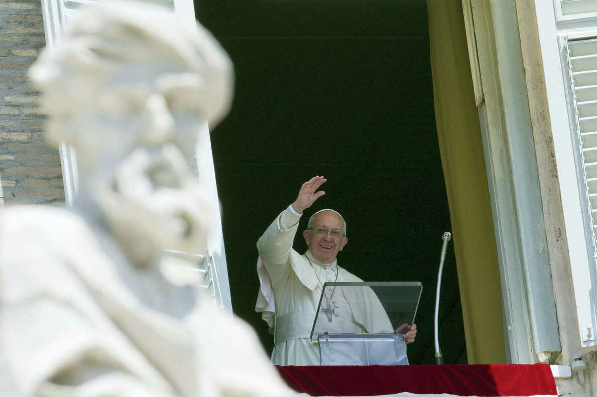 Pope Francis delivers his blessing during the Angelus noon prayer he celebrated from the window of his studio overlooking St. Peter's Square at the Vatican Sunday.