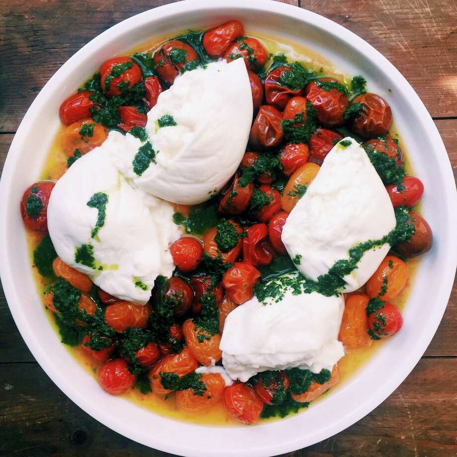 If you have never tried burrata, go out and find some and then make roasted cherry tomatoes with burrata and basil oil. Photo: Katie Workman — The Associated Press   / Katie Workman