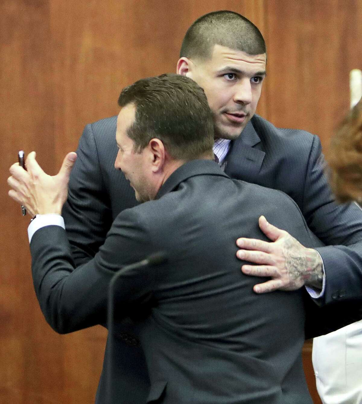 Former New England Patriots NFL football player Aaron Hernandez, left, hugs his attorney Jose Baez during a status conference in his upcoming double murder trial, Wednesday, Oct. 5, 2016, at Suffolk Superior Court in Boston. Hernandez, who has pleaded not guilty, is scheduled to stand trial in February in the 2012 killings of two men he encountered in a Boston nightclub. He is already serving a life sentence in the 2013 killing of Odin Lloyd, a semi-professional football player.