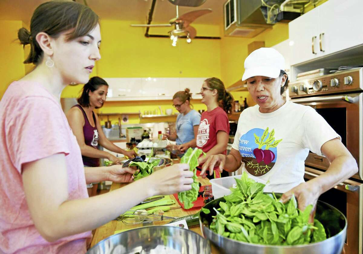 (Peter Hvizdak - New Haven Register) Celin Garcia, New Haven Farms cooking and nutrition educator, far right, with volunteers Cara Dougan of New Haven, Rachel Clare of West Haven, Jamie Cooper of New Haven, and Julia Berkman Hill of New Haven as they prepare food at the CitySeed commercial kitchen Thursday, June 30, 2016 for a New Haven Farms Eating Healthy cooking class.